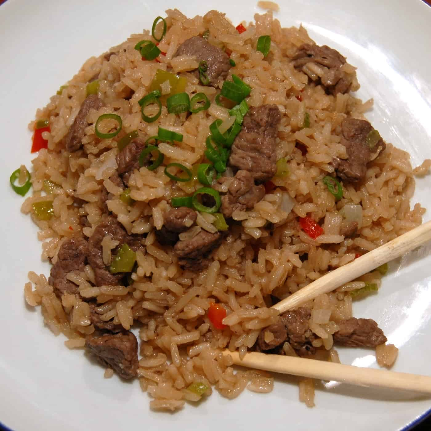 Beef fried rice serve with green onion and chopsticks